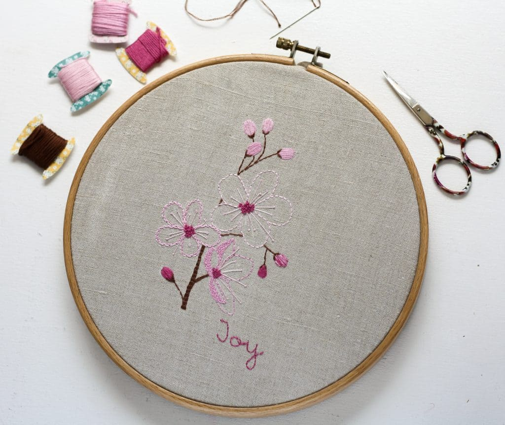 hand embroidered spring blossoms and buds in an embroidery hoop